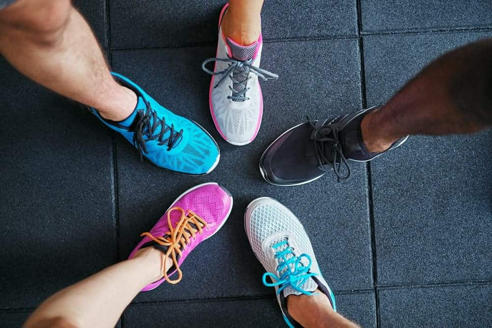 A look at various running shoes on a dark tiled floor.