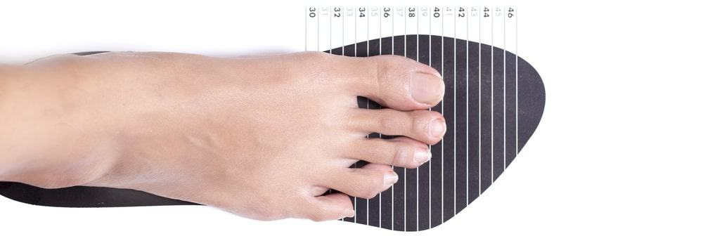 This is a close look at a woman measuring her shoe size.