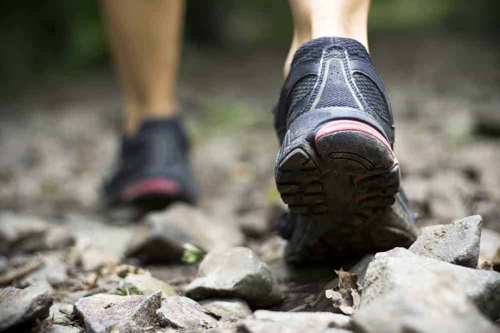 This is a close look at a woman hiking with running shoes on.