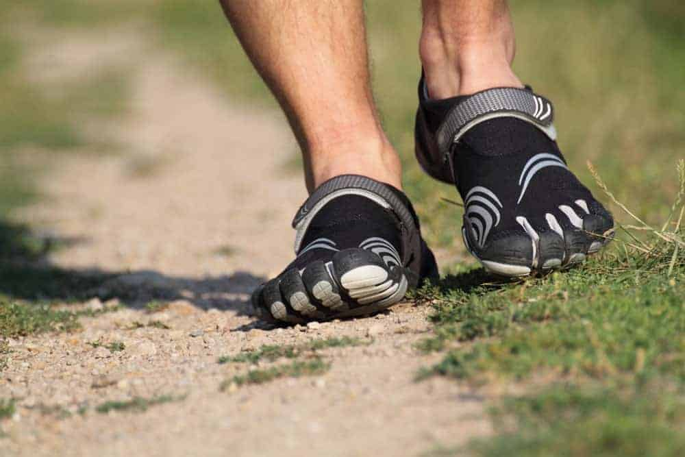 This is a close look at a man wearing a pair of toed shoes.