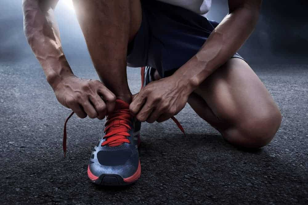 This is a close look at a man tying his running shoes.