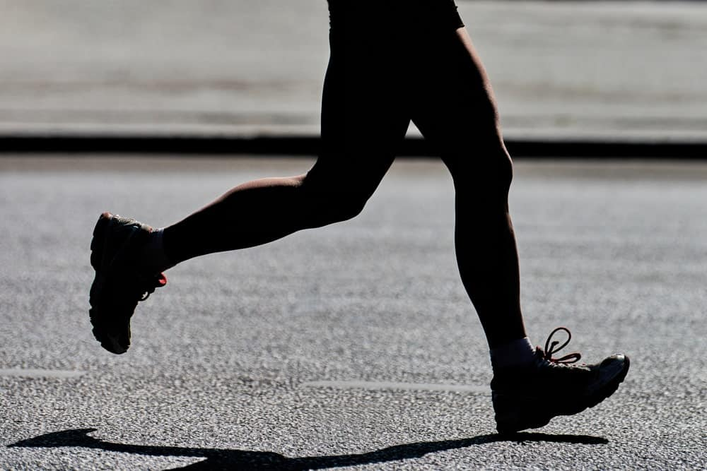 This is a close look at a woman running on an asphalt road.
