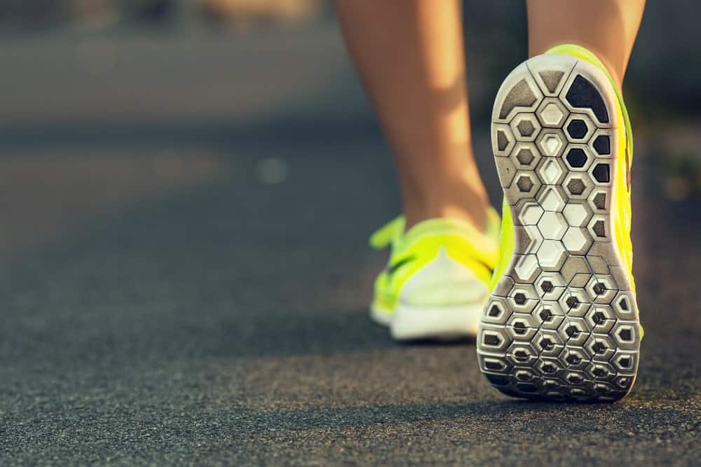 A close look at a woman wearing road running shoes.