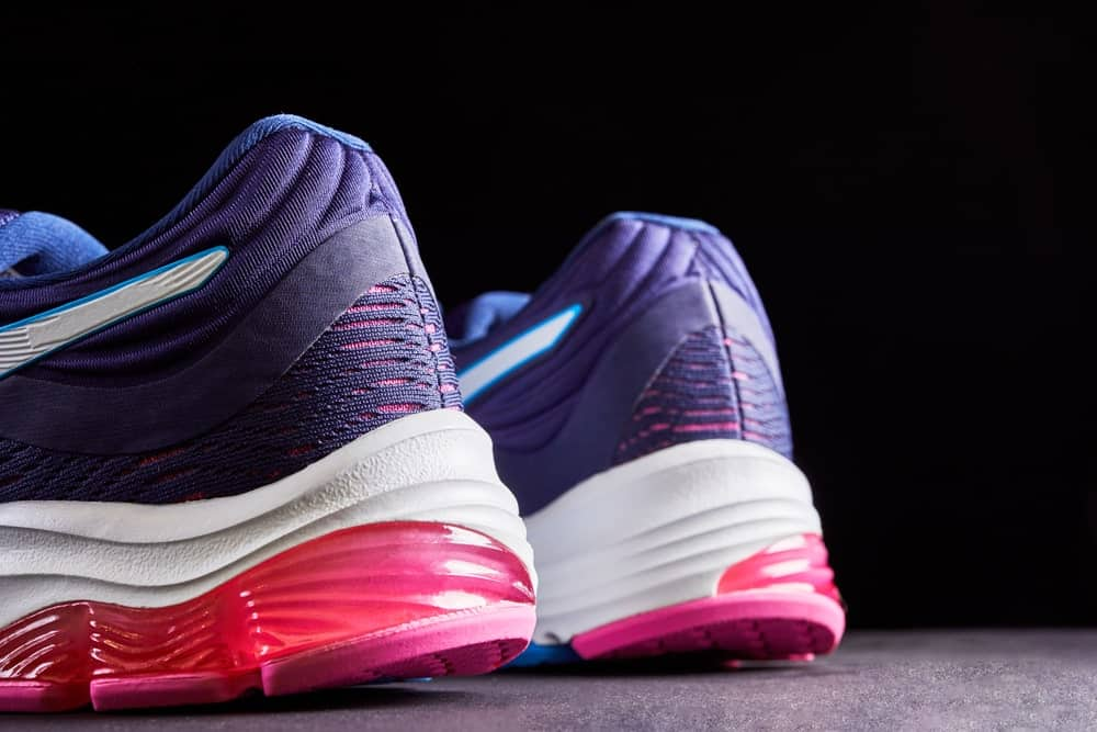A close look at a pair of purple and pink running shoes.