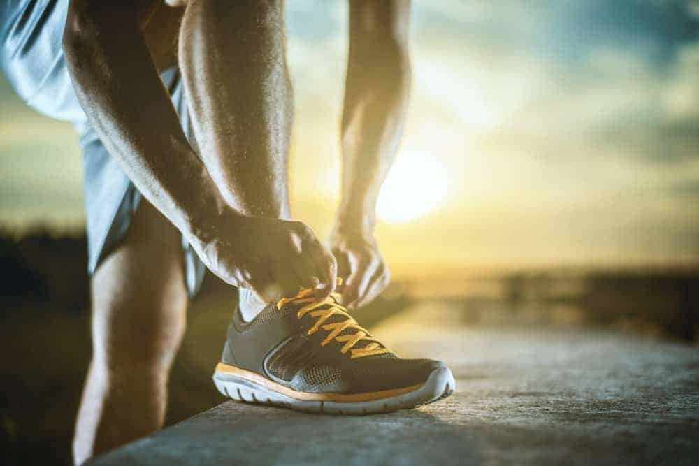 This is a close look at a man tying the laces of his running shoes.