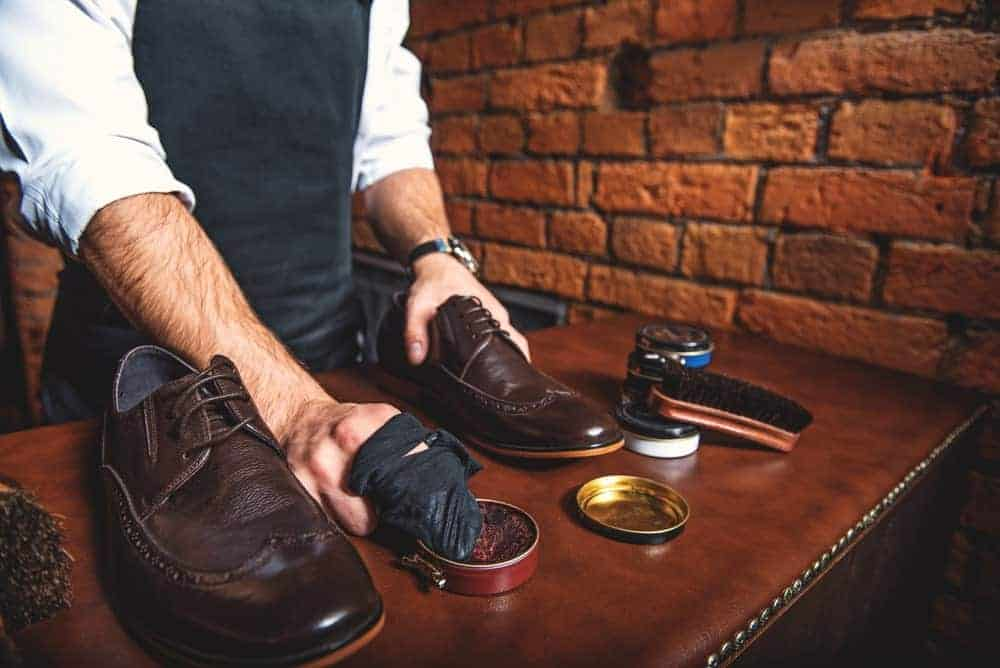 This is a close look at a man polishing his leather shoes.