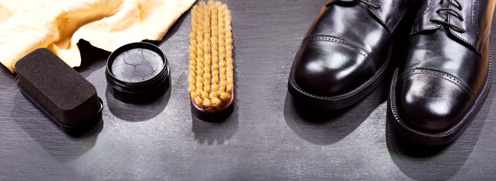 A close look at a pair of leather shoes with a set of wax shoe polish.