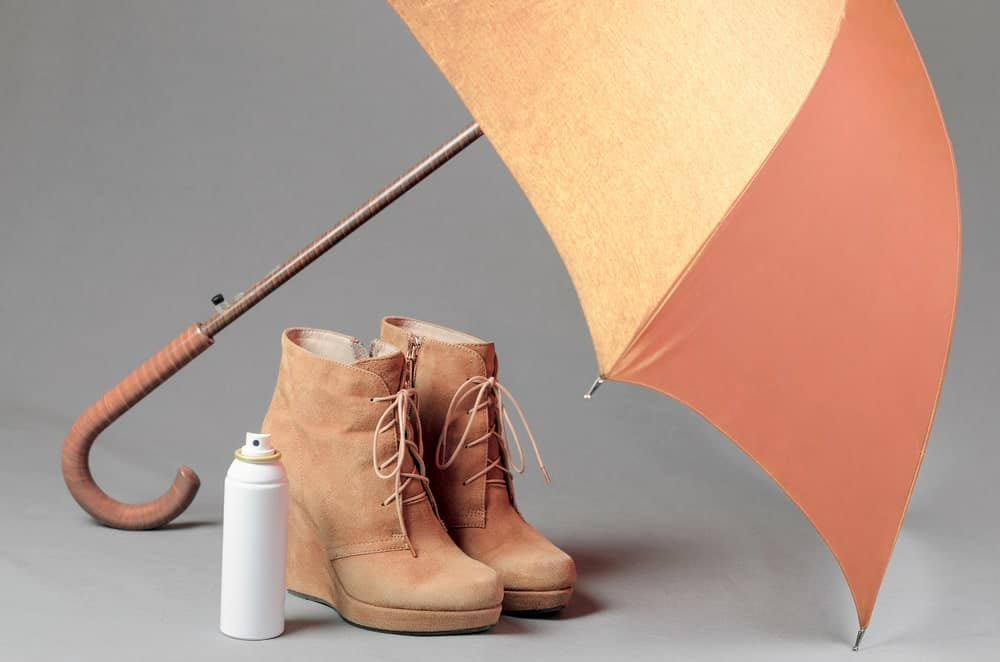 A pair of leather shoes with an umbrella and a leather conditioner.