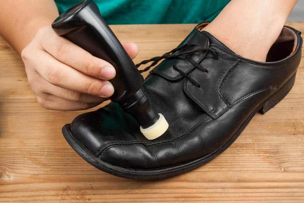 A man polishing a black shoe with liquid shoe polish.