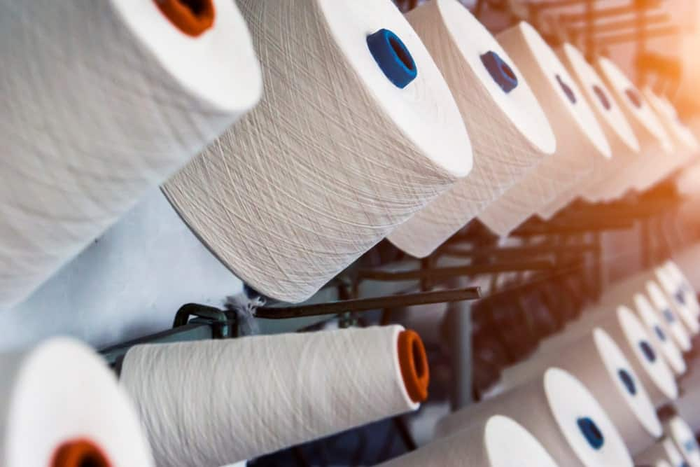 A close look at spools of white cotton thread.
