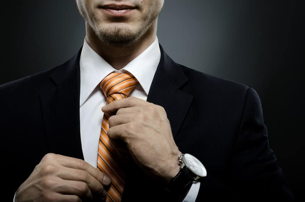 Man in black suit holding his orange striped necktie.