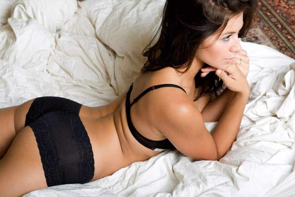 A woman relaxing on the bed wearing a pair of boyshort panties.