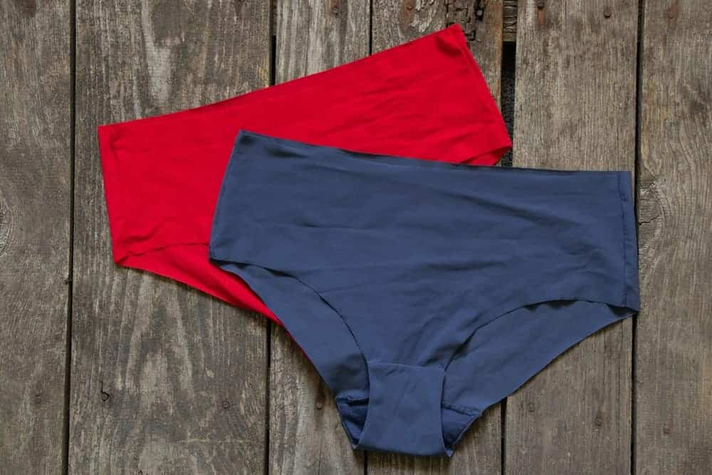 Red and blue seamless women's briefs on a wooden floor.