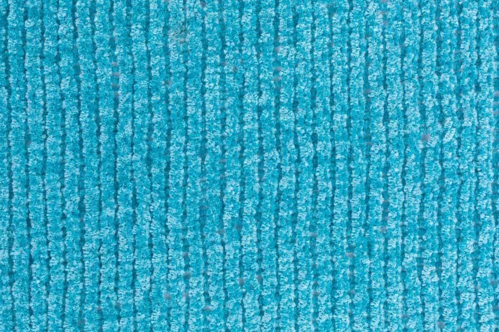 A close look at a bright blue chenille yarn cloth.