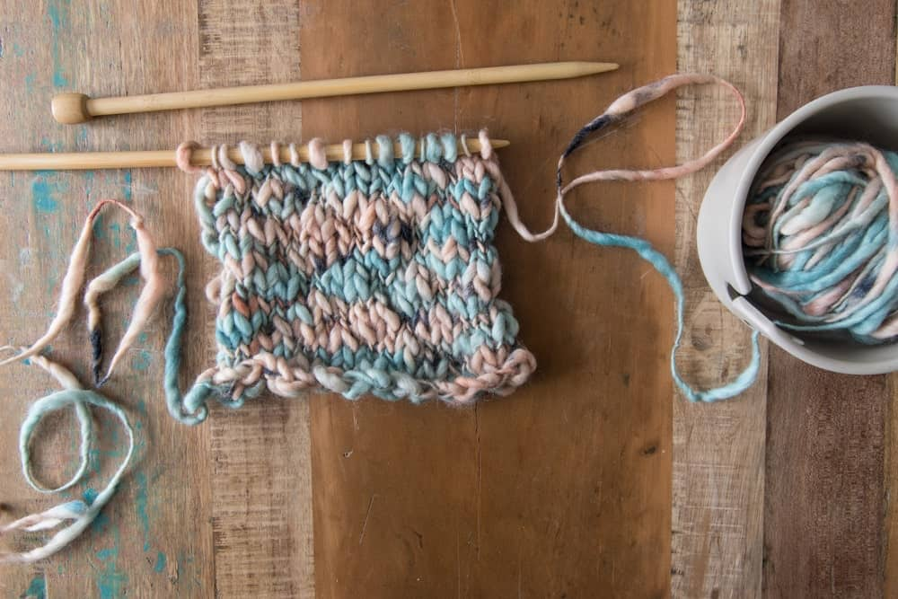 An unfinished knitting project using thick-thin yarn.