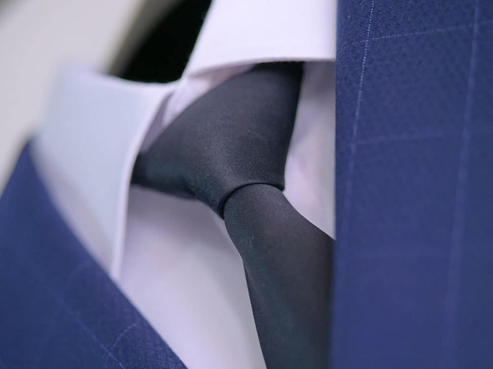 Navy blue suit with white shirt and embroidered silk necktie in Windsor knot.
