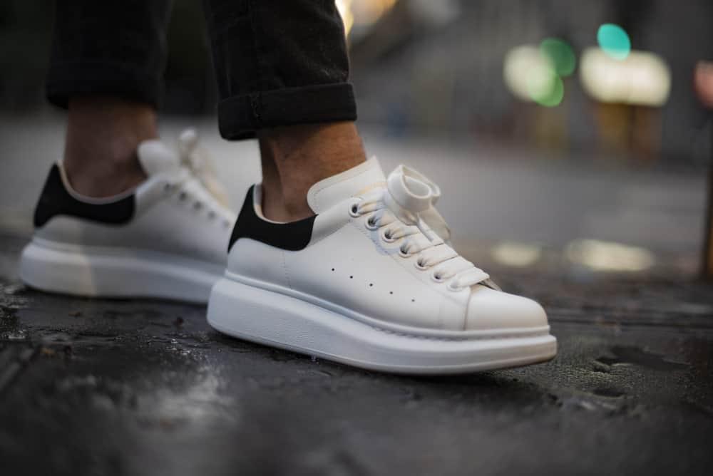 Man wearing a pair of Alexander McQueen sneakers in the street.
