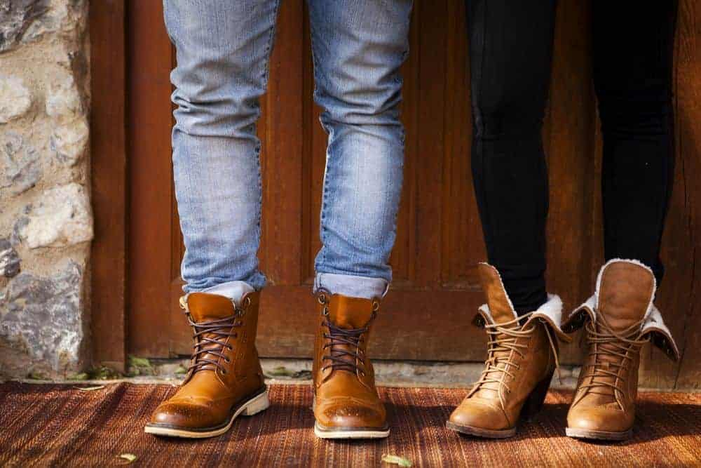 Couple's feet wearing brown leather boots.