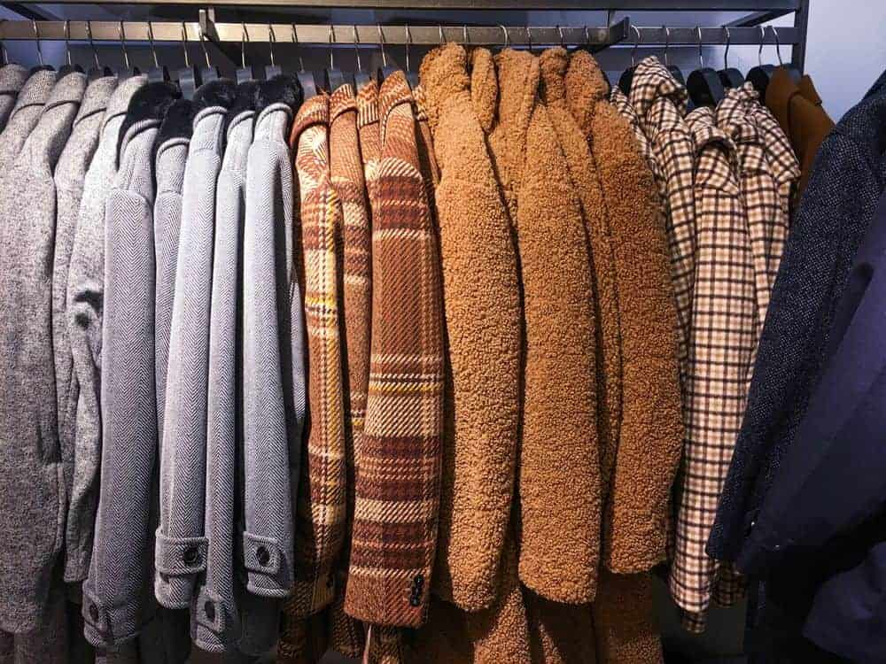 Various coats and jackets on hangers in a store.