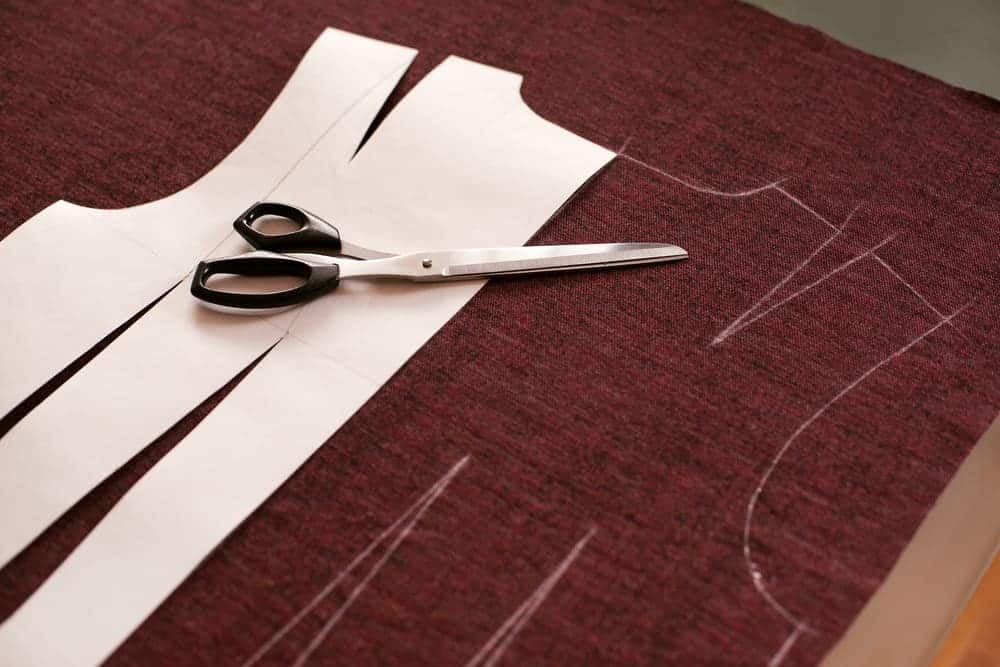 Cut out sewing pattern and tailoring scissors over a brown fabric.