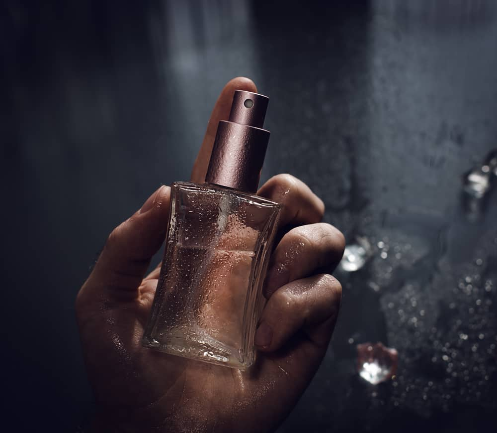 A hand holding a perfume.