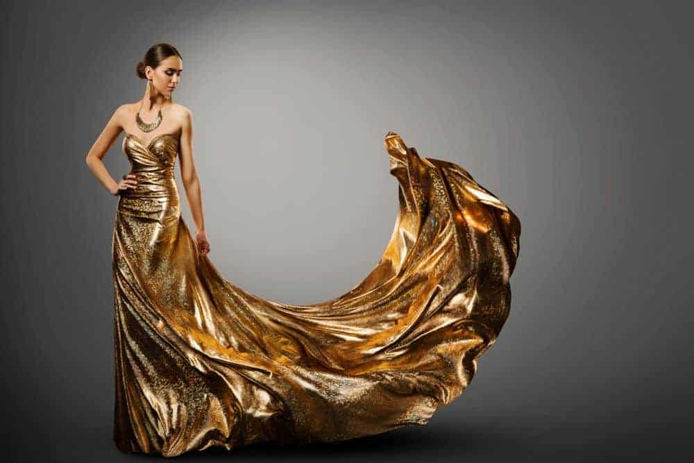Woman wearing a long, waving, and fluttering gown in gold.