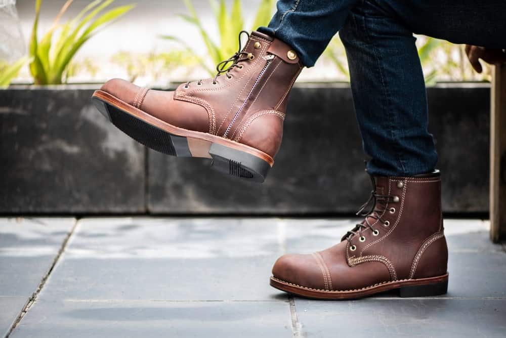 This is a close look at a man wearing a pair of brown leather boots with his jeans.