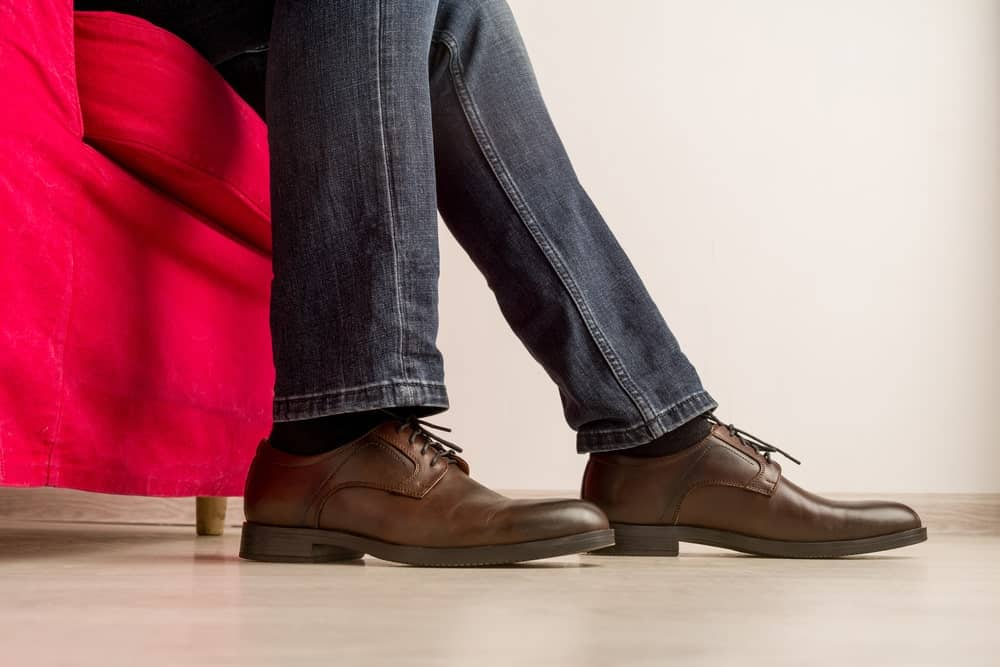 This is a close look at a man wearing a pair of jeans and a pair of dress shoes.