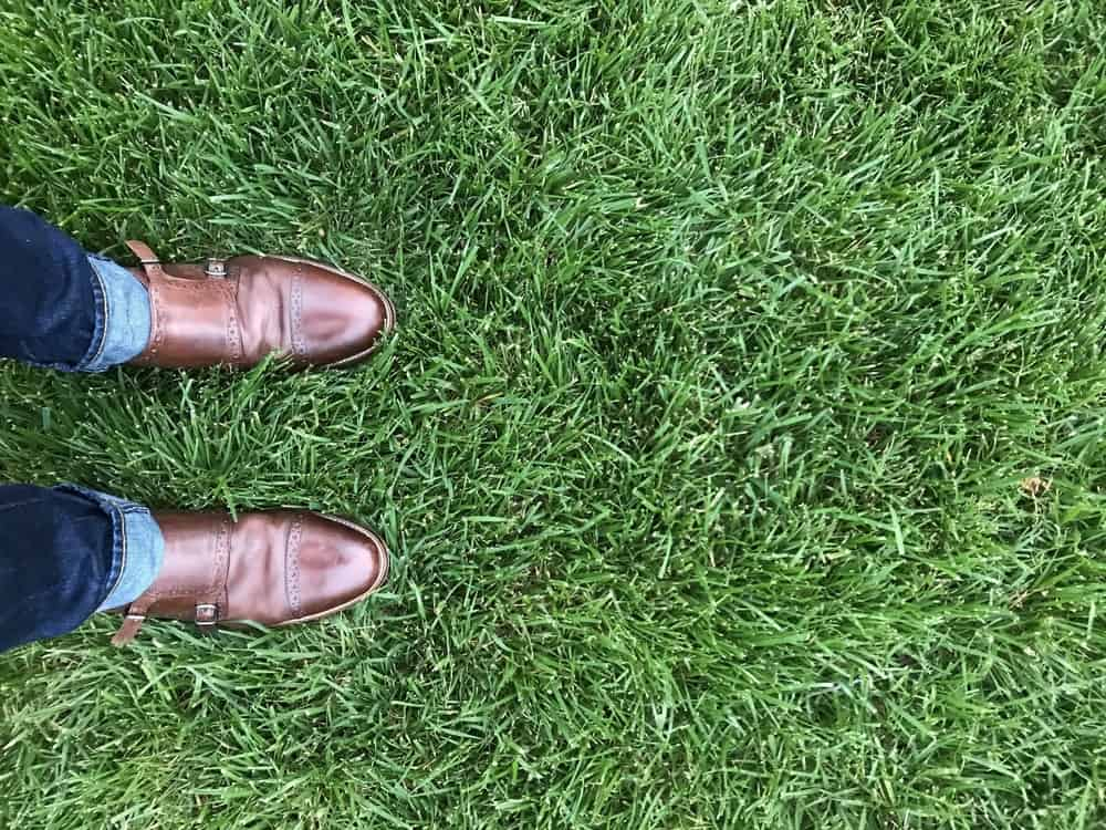 A close look at a man wearing brown leather monk-strap shoes with his jeans.