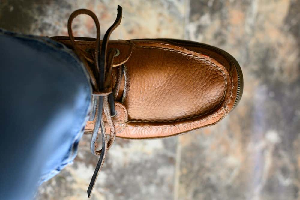 A close look at a man wearing brown leather boat shoes with his jeans.