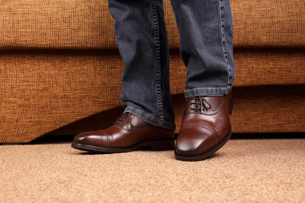 This is a close look at a man wearing jeans and a pair of oxford shoes.