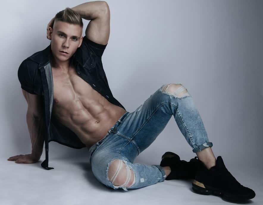 A model sporting a pair of ripped jeans and a pair of black trainers.