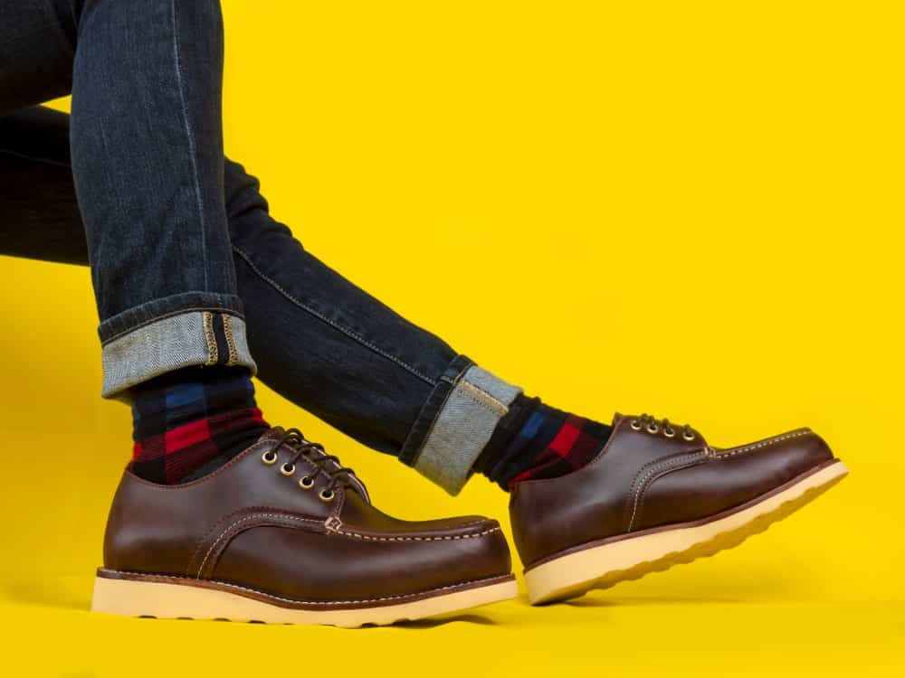 This is a close look at a man wearing a pair of brown leather derby shoes and jeans.