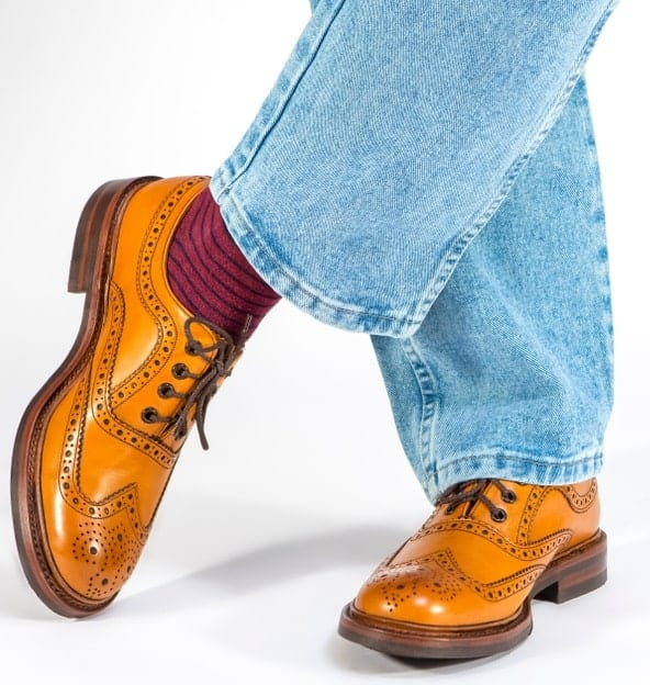 This is a close look at a man wearing a pair of brogue shoes with his jeans.