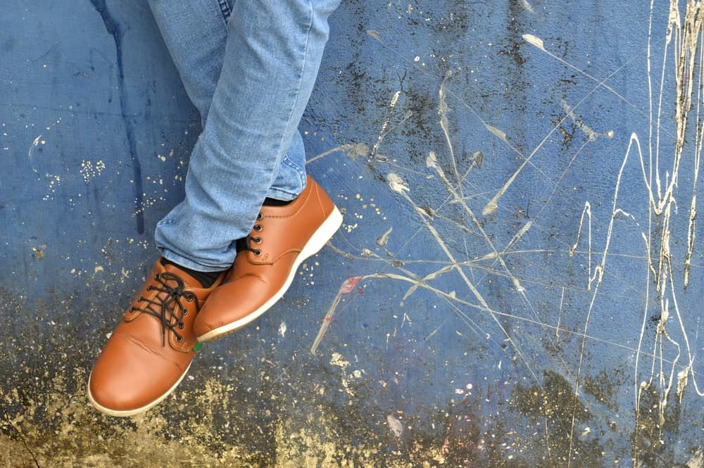 A close look at a man wearing brown leather shoes with his jeans.