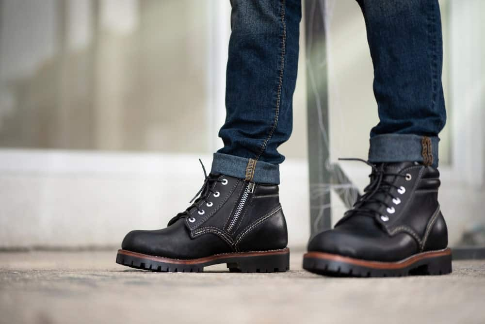 A close look at a man wearing boots with his jeans.