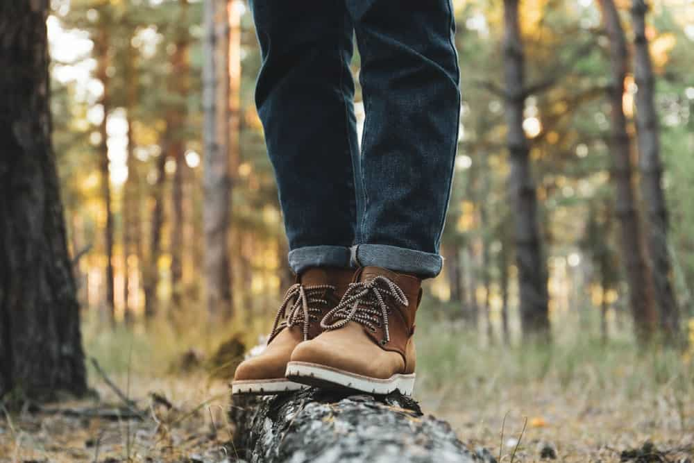 A man in the woods wearing a pair of hiking boots and jeans.