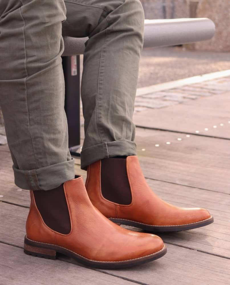 A man wearing a pair of brown leather Chelsea boots with his jeans.