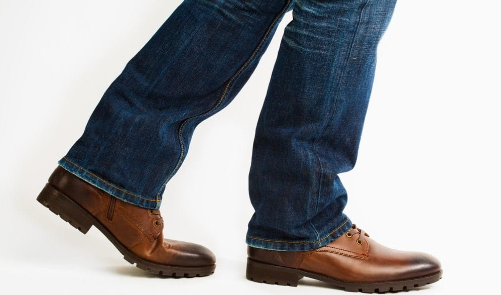 A close look at a man wearing brown leather walking shoes with his jeans.