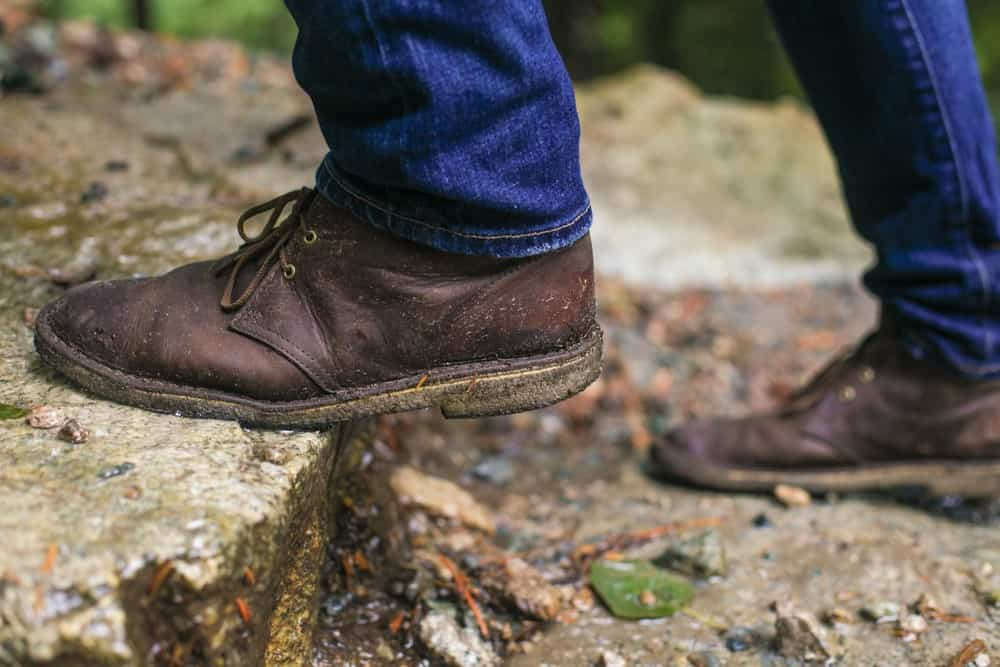 A close look at a man wearing dark brown chukka shoes with his jeans.