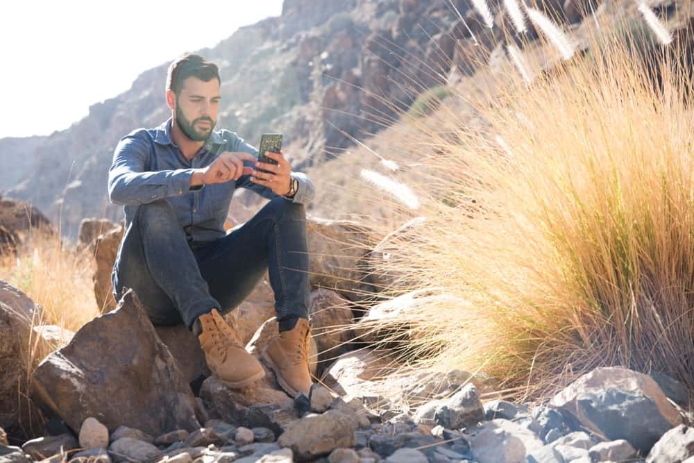 A man sitting on a rock wearing a pair of jeans and desert boots.