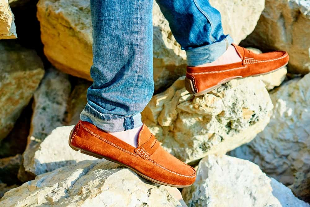 A man wearing a pair of loafers with his jeans.