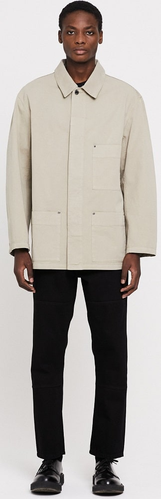A man wearing the excursion garment dyed beige from Etudes.