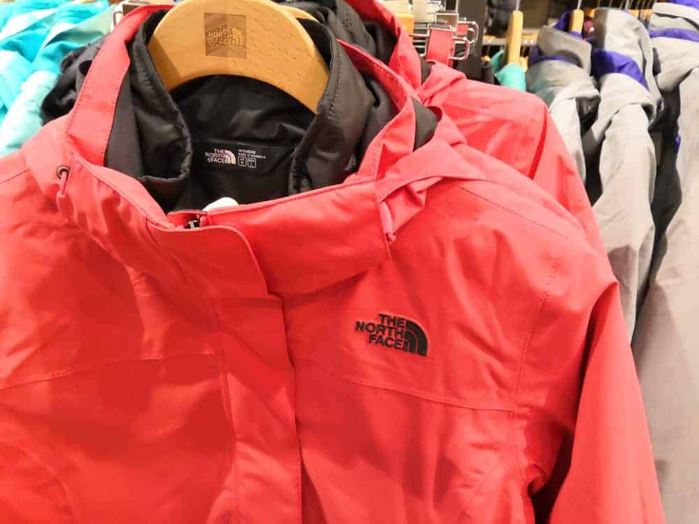 The North Face jackets on hangers in a store.