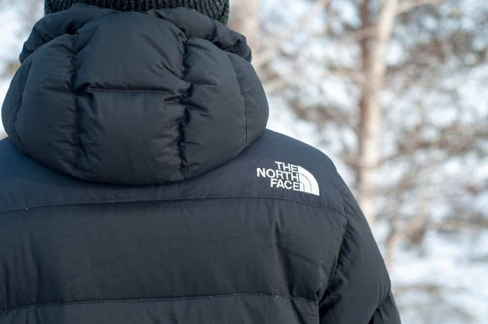 Back profile of a man wearing The North Face jacket with hoodie.
