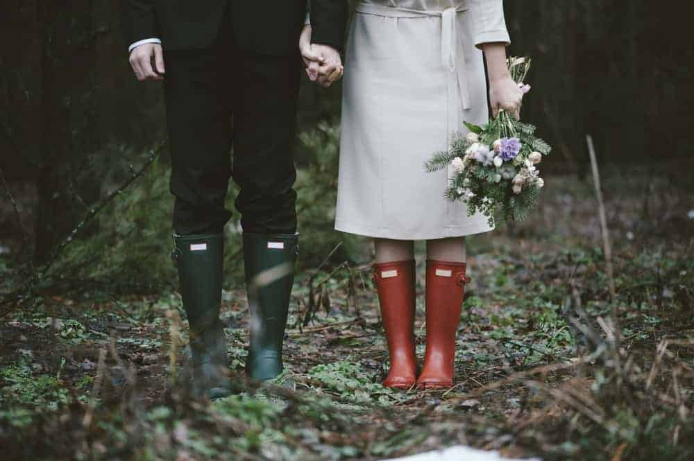 A couple in the middle of a forest wearing green and red boots.