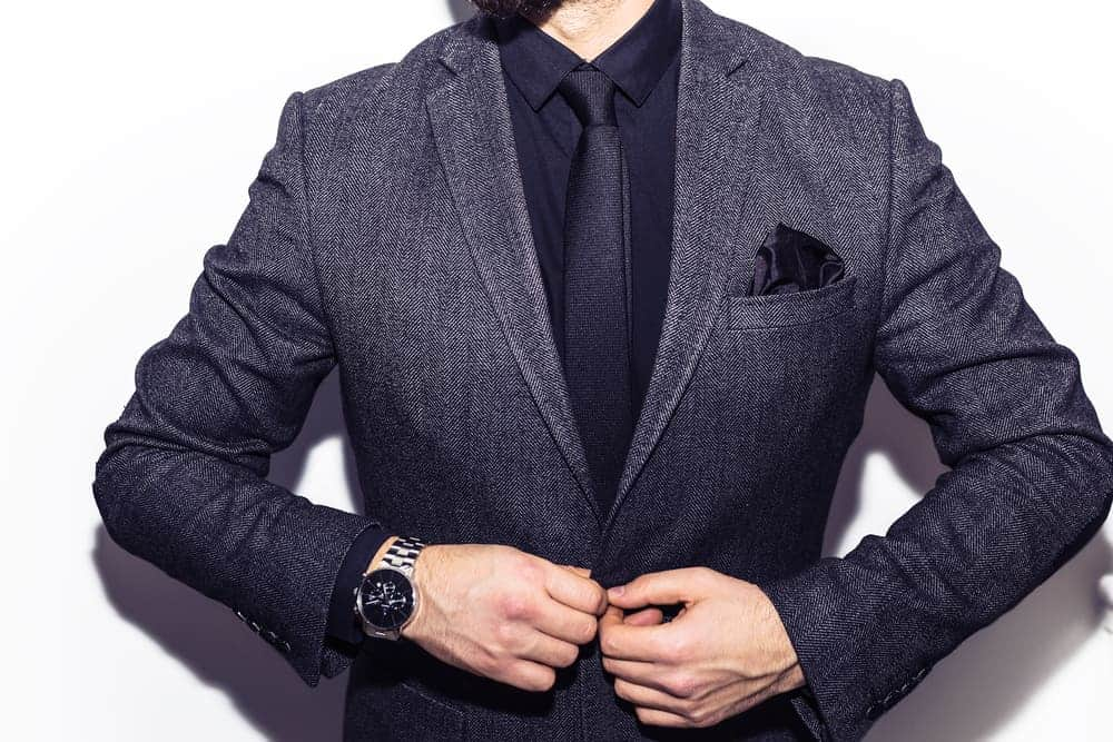 A close look at a man buttoning his charcoal black suit.