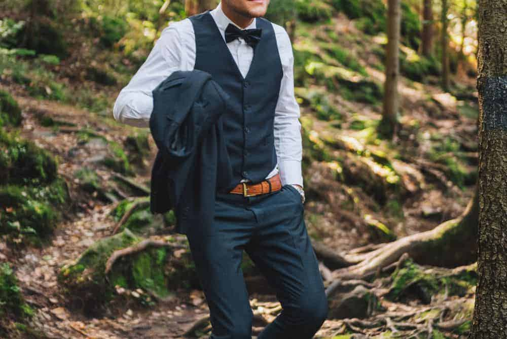 Groom in the middle of a forest wearing three piece black wedding suit with a bowtie.