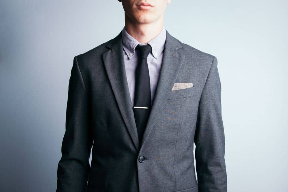 A young man sports a two piece, grey suit with a tie and pocket square.
