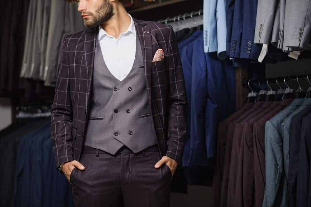 Man in a boutique wearing a classic plaid suit.